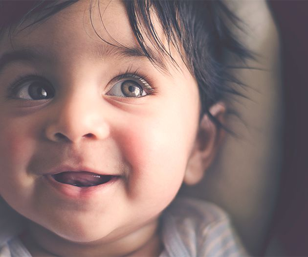Close up of baby smiling and looking up