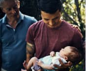 Dad holding newborn surrounded by family