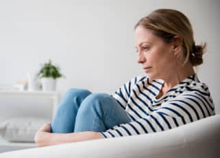 Woman sat on the sofa looking depressed
